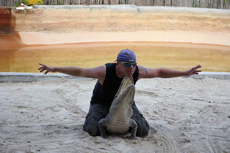 Showman holding alligator with the chin